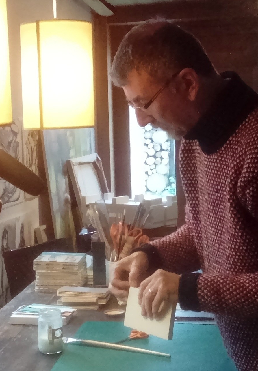 Bookbinder Ken Futers is pasting a headband on to the spine of the bookblock.